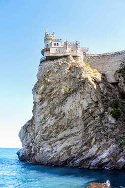 The castle is on top of a rocky cliff.