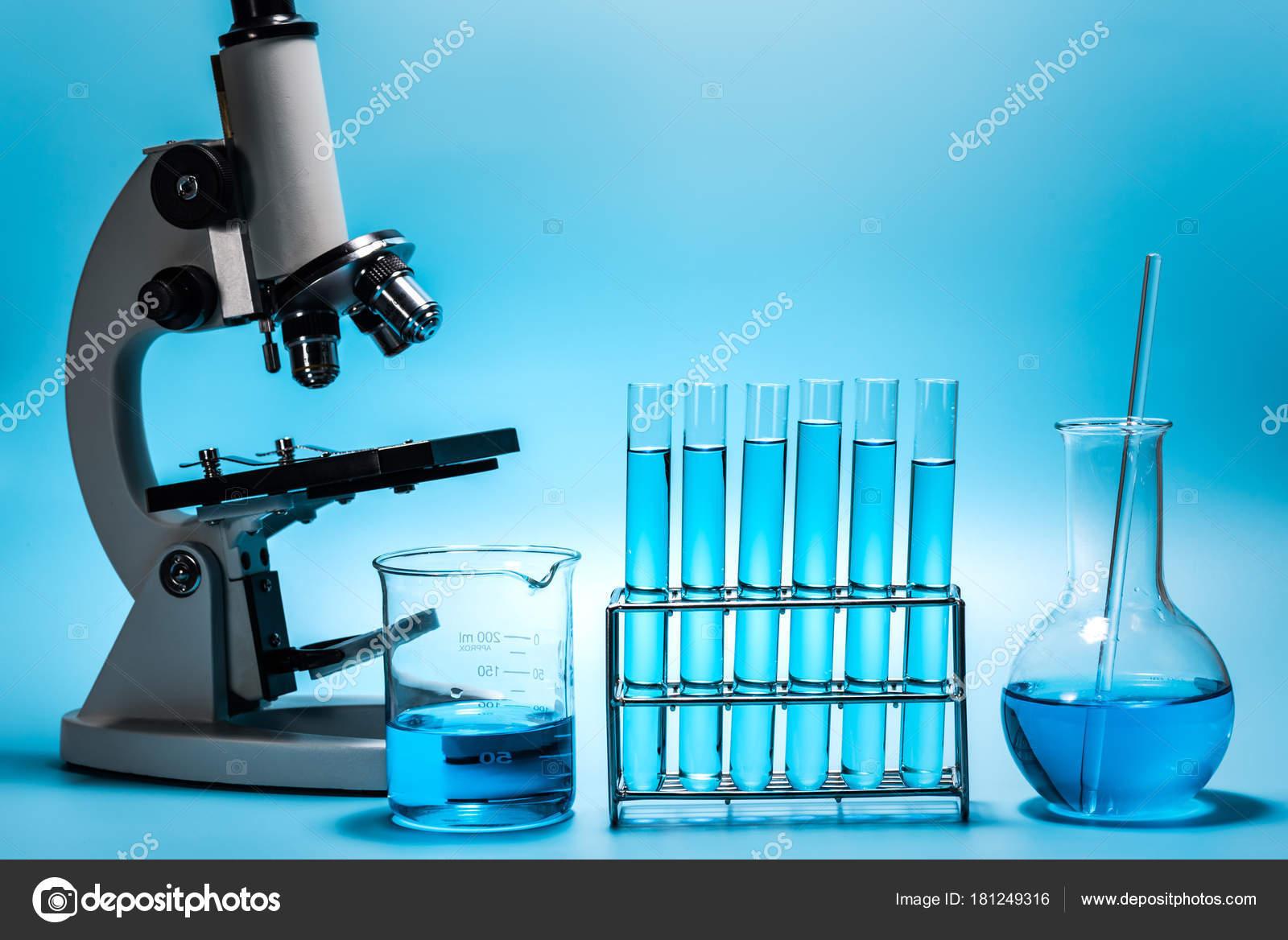 Mikroskop und labor reagenzglas auf hellblauem grund s