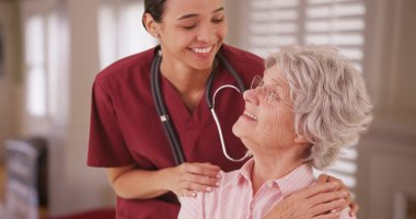 Hispanic female nurse looking and smiling with senior caucasian woman