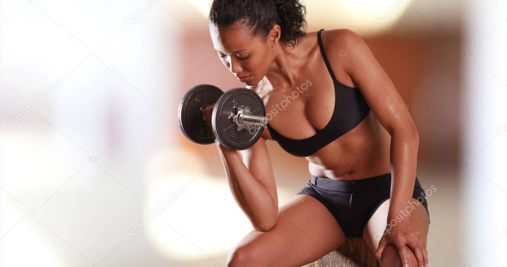 Mixed-race millennial womanlifting weights at the gym