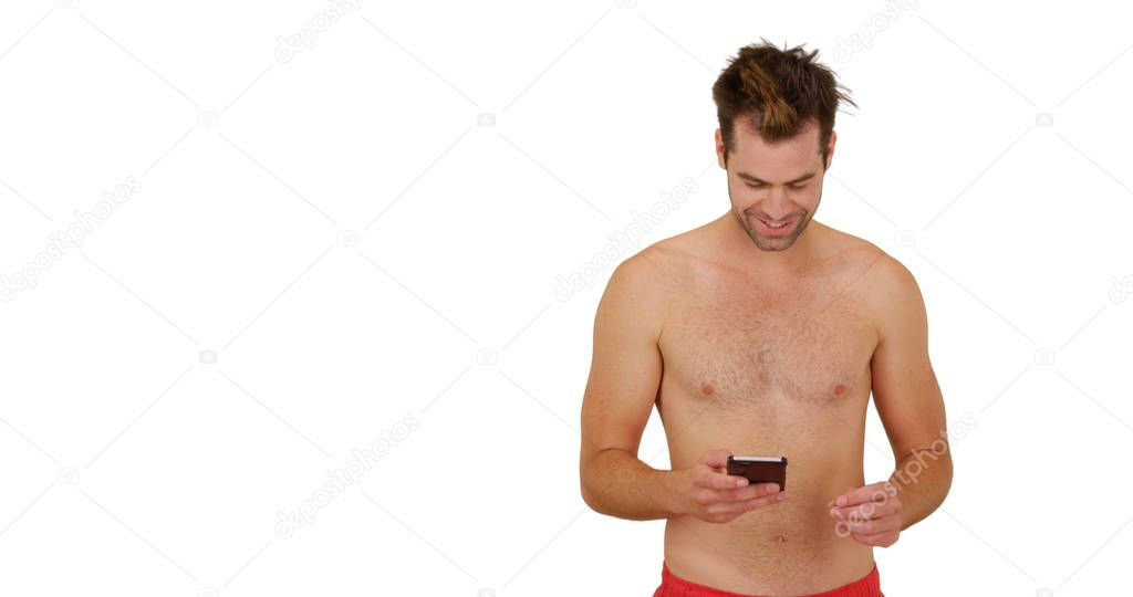 Young happy white guy with smartphone in front of white background in swimsuit