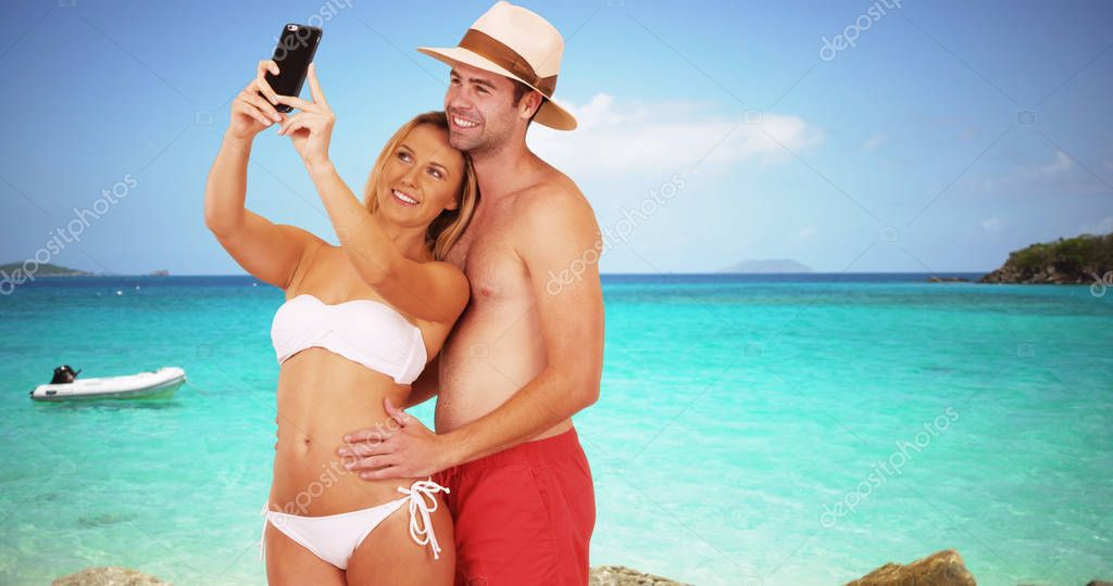Happy millennial couple taking selfies by the beach