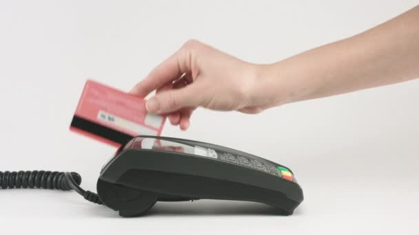Female hands swipe credit card at Pos terminal.
