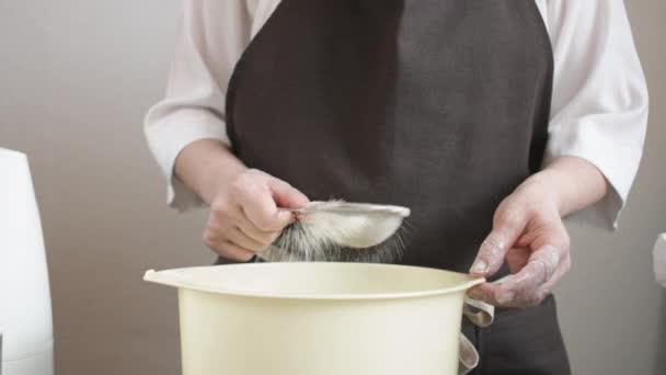 Weibliche Hände siebt das Mehl