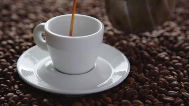 Pouring cup of hot coffee and roasted coffee beans