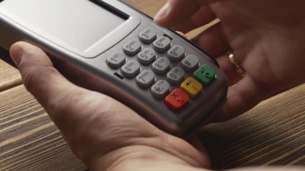 Person pushing the button and swipe credit card payment on pos terminal