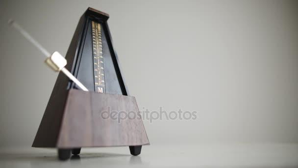 Vintage metronome with golden pendulum beats slow rhythm