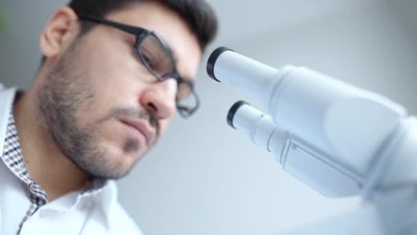mladý vědec při pohledu přes mikroskop