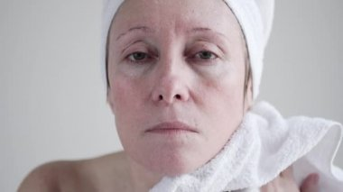 Caucasian mid age woman applying cream to her face.