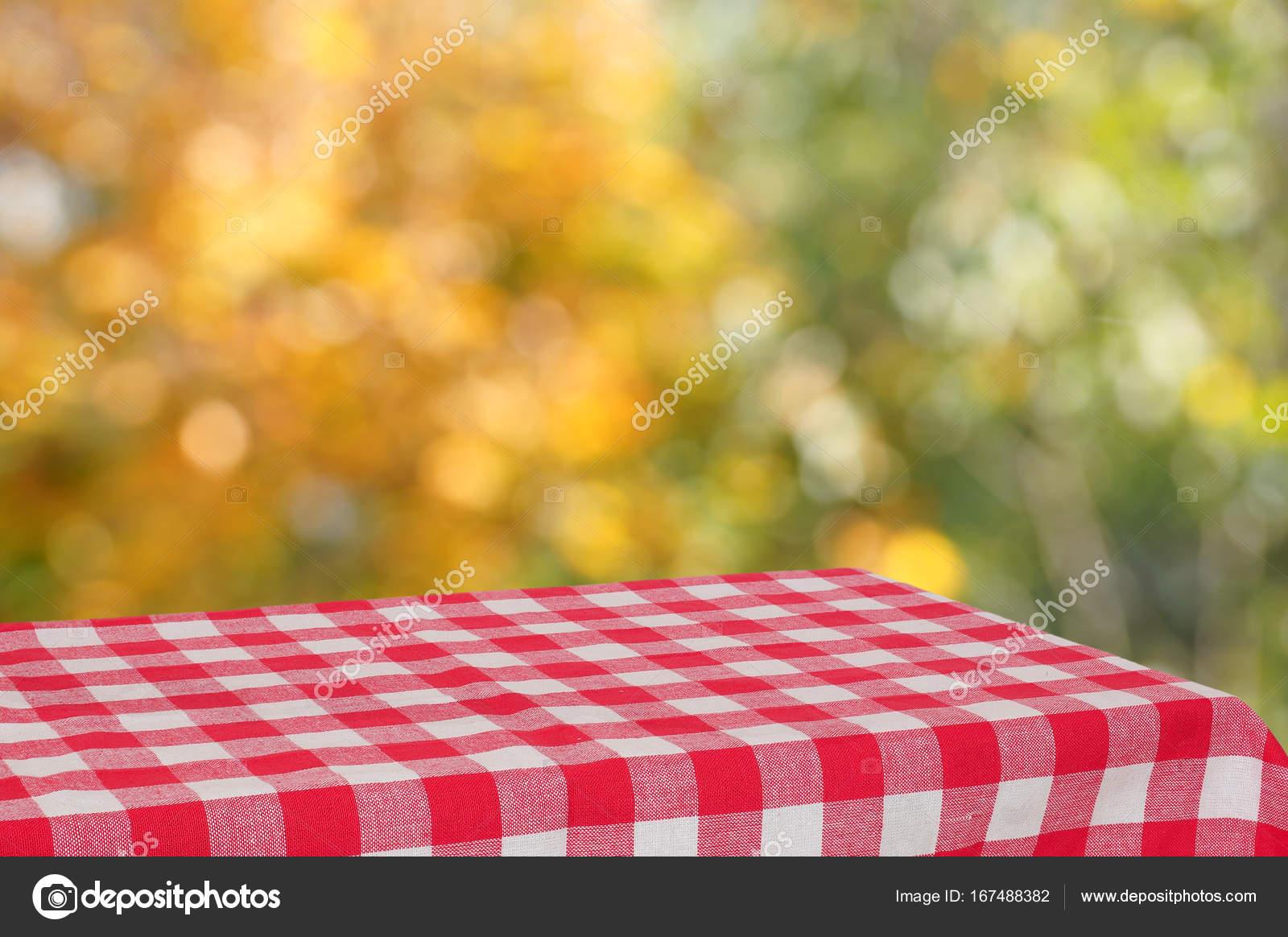 Leere Tabelle mit einem rot karierten Tuch im Herbst Garten. Der ...