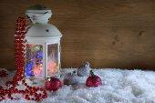 Vánoční lucerny a koule dřevěné zdi. Nový rok složení. Lucerna s věnec a koule na sněhu