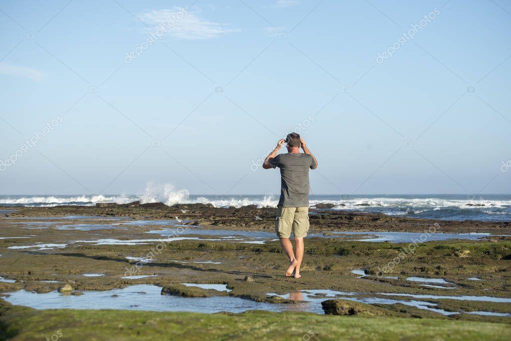 Man walking along on the rocks