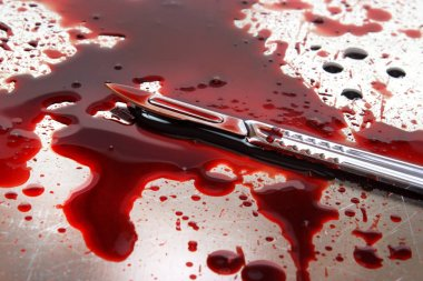 Surgeon knife on stainelss steel autopsy table with lot of blood