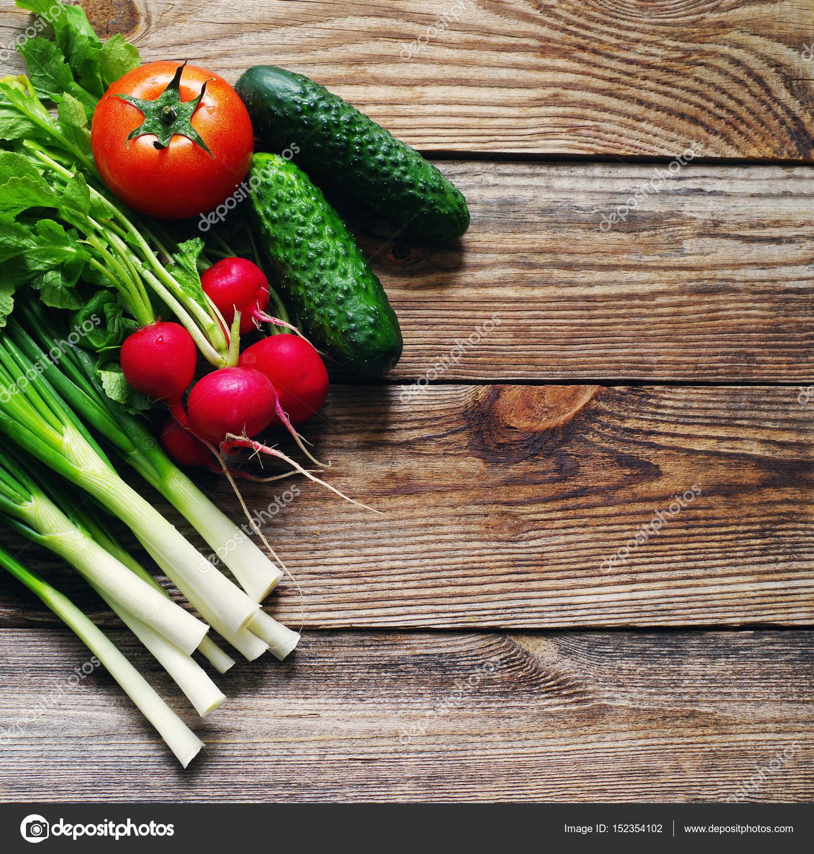Fresh green onions, garden radish, cucumbers and tomato on a wooden ...