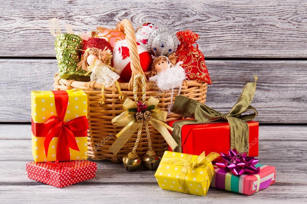 Viele Weihnachtsgeschenke in der Nähe von den Korb mit Kugeln ...