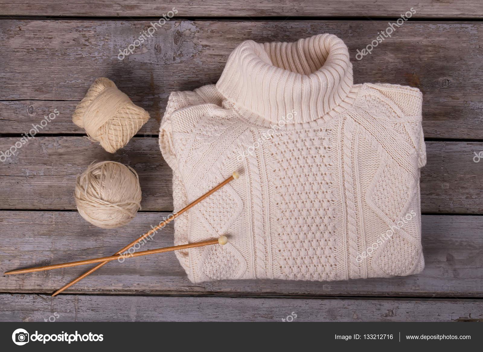 f4cc5f59cf90 ... φόντο ξύλινη — Φωτογραφία Αρχείου · Ζεστά πλεκτά πουλόβερ σε ένα ξύλινο  υπόβαθρο. Χειμώνας πουλόβερ με νήματα και βελόνες πλεξίματος.