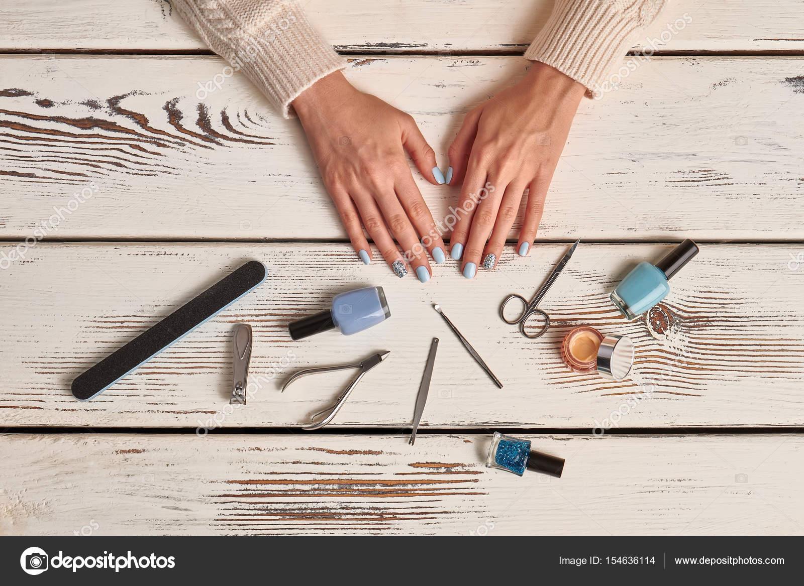 Schöne gepflegte Frau Nägel mit blauen Nagellack und Werkzeug ...