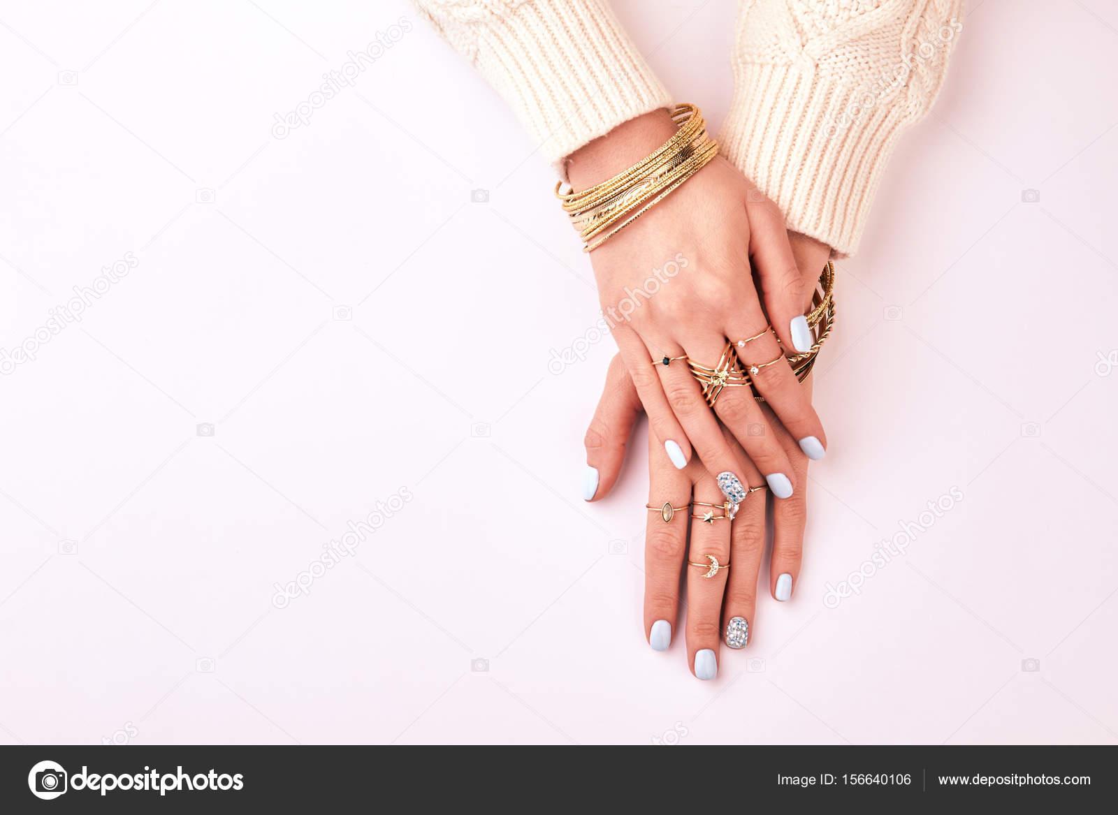 Γυναικεία χέρια σε δαχτυλίδια και βραχιόλια σε λευκό φόντο– εικόνα αρχείου 6e12491ad5a