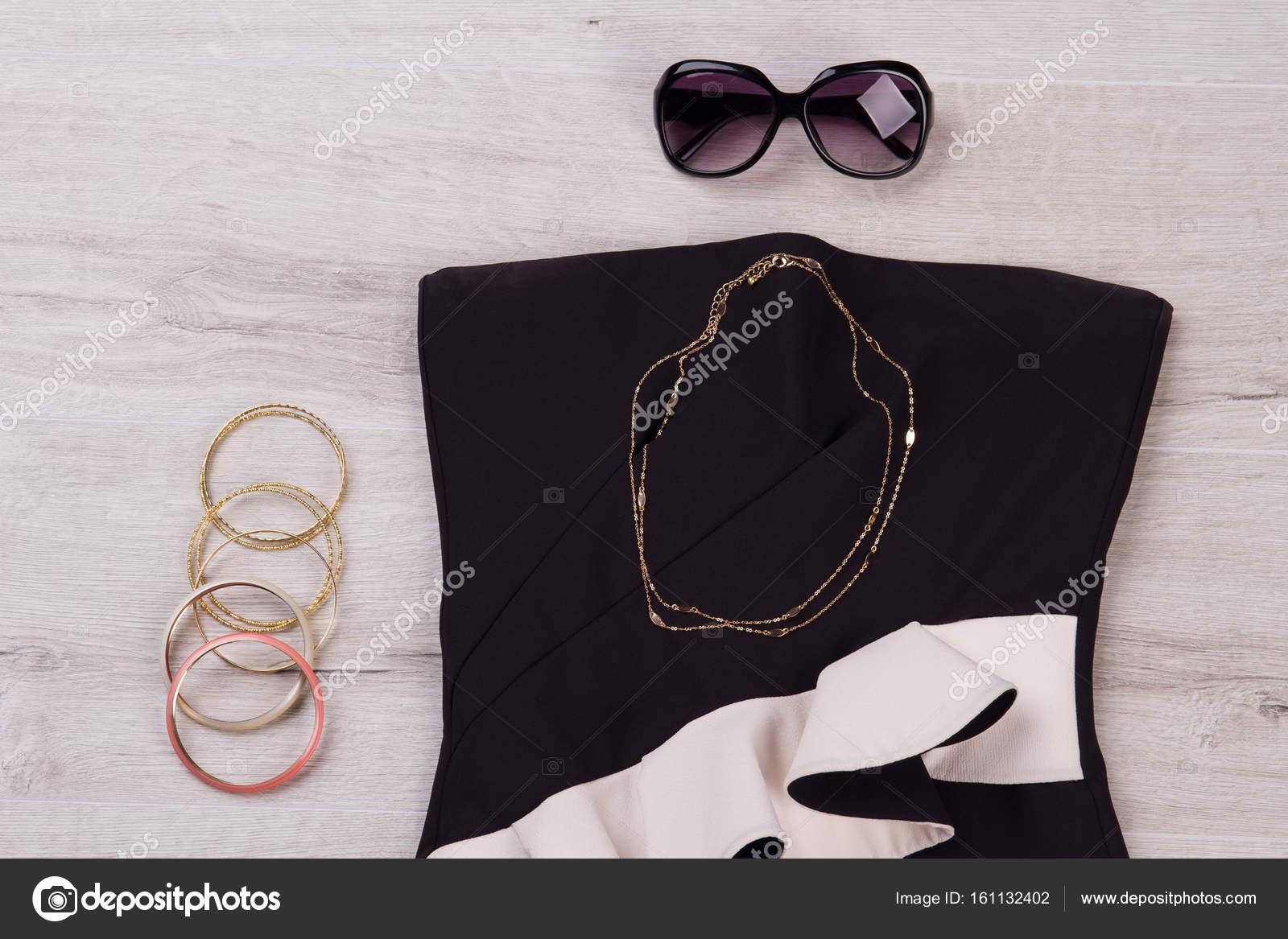 Abito nero con occhiali da sole e gioielli su un fondo di legno