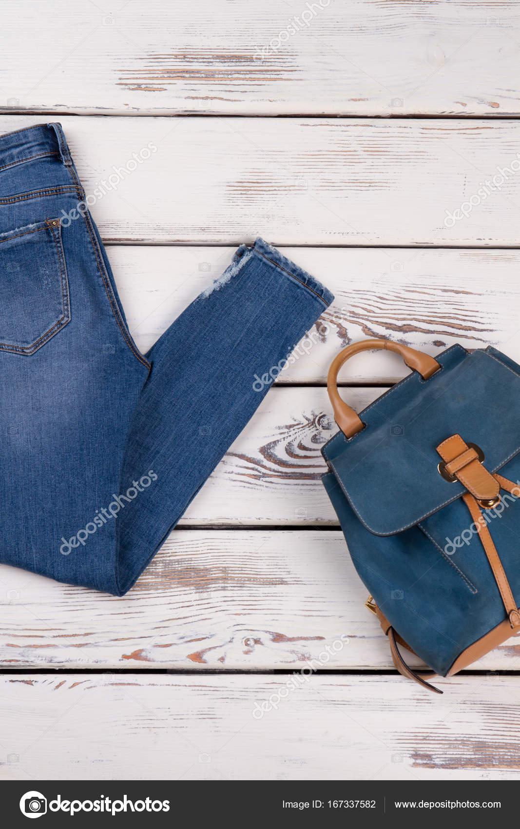 eb6935dee855 Μπλε τζιν και δερμάτινη τσάντα σε ξύλινο πάτωμα. Σετ μοντέρνα ρούχα.  Λεπτομέρειες των γυναικών καθημερινά look — Εικόνα από margostock
