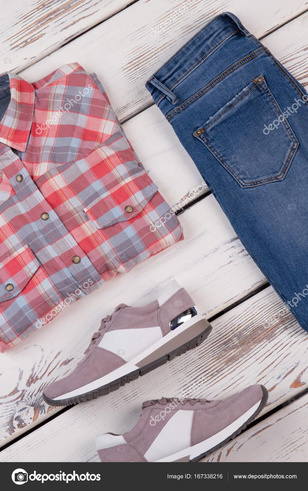737df3cb5107 Κολάζ από μοντέρνα γυναικεία ρούχα σε παλιό ξύλινο υπόβαθρο. Καρό πουκάμισο  σε συνδυασμό με τζιν και αθλητικά παπούτσια — Εικόνα από margostock