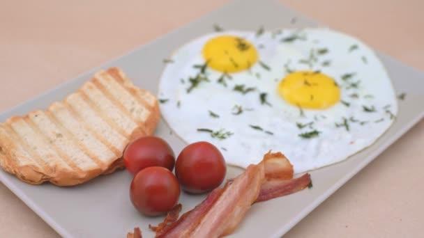 Snídaně na tác se slaninou a vejci, rajčaty a tousty. Pomalé načítání