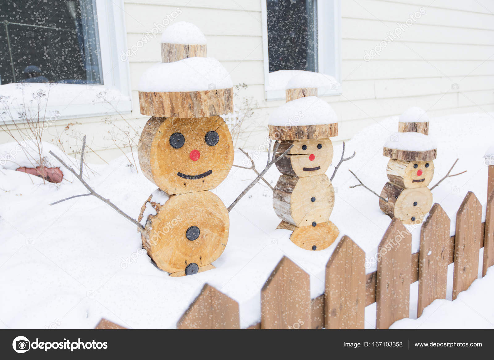 a snowman made in piece of wood with fence on the front photo by lopolo