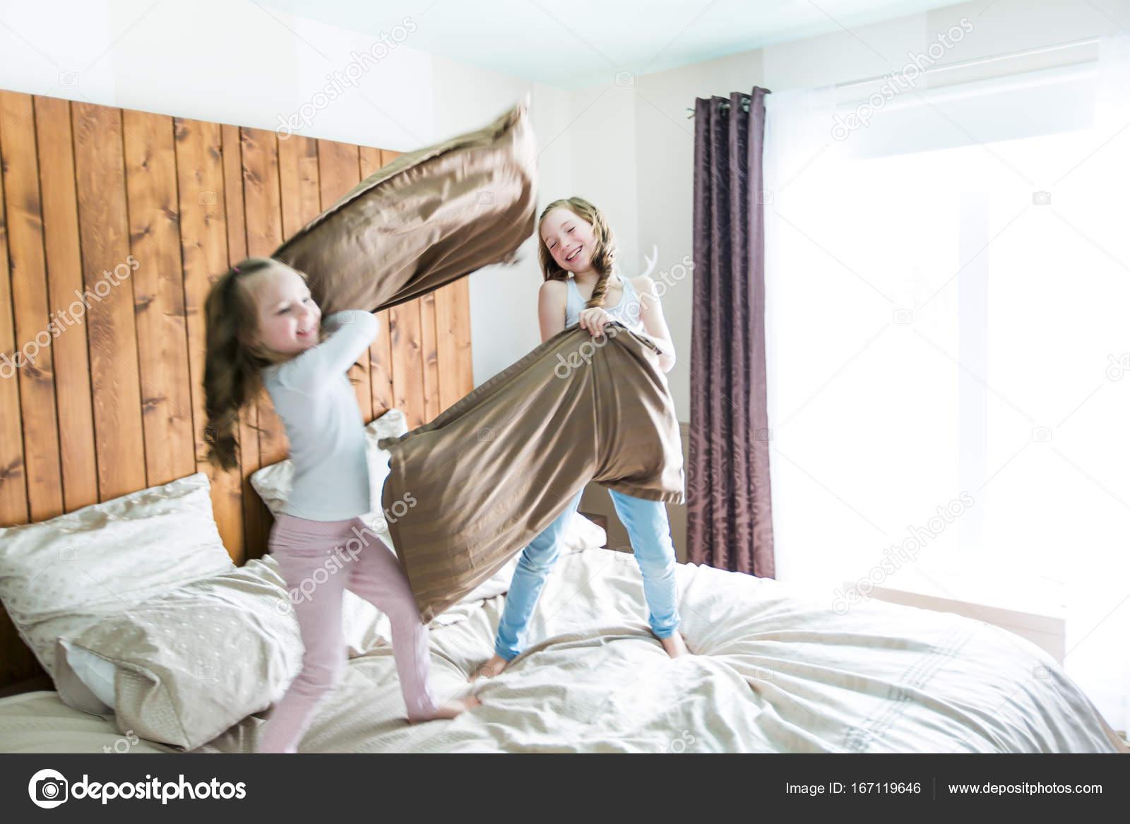 Portret kinderen vechten met kussens in bed u stockfoto lopolo