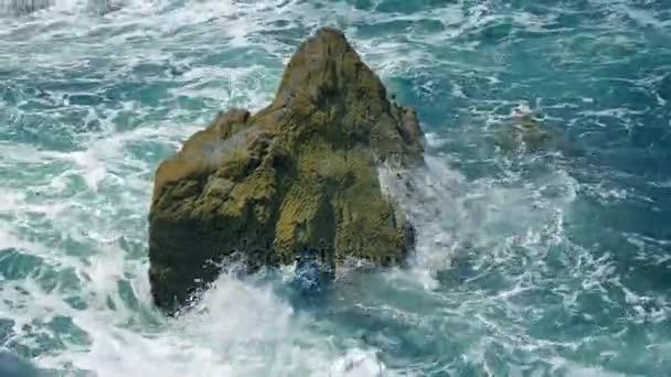 Vlny tříštící skály v moři