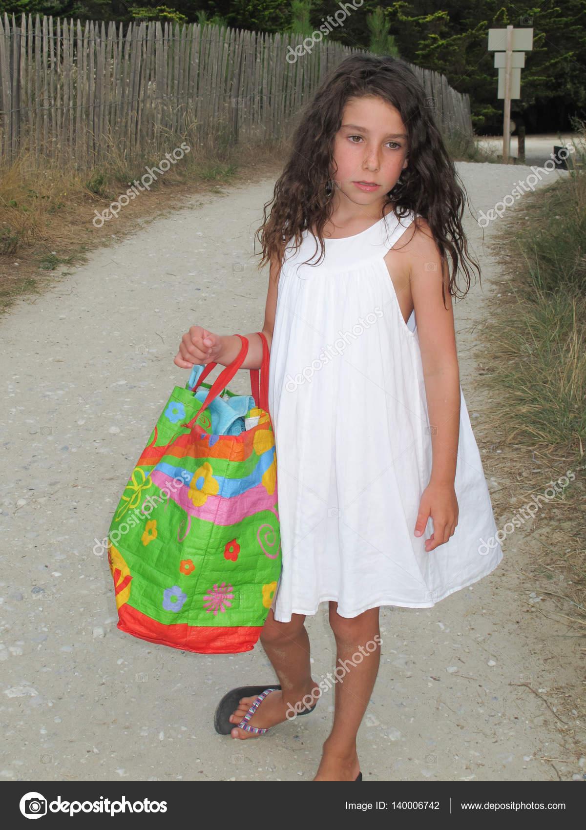 Niña Con Vestido Blanco Con Su Bolso A La Playa Foto De