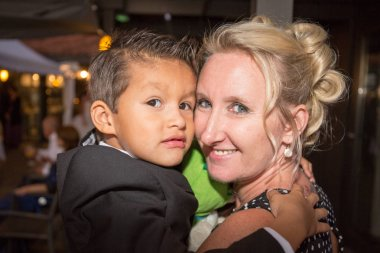 Blonde Mother wears her mixed son in her arms at night