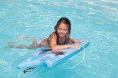 dítě dívka hraje v bazénu s modrým bodyboard