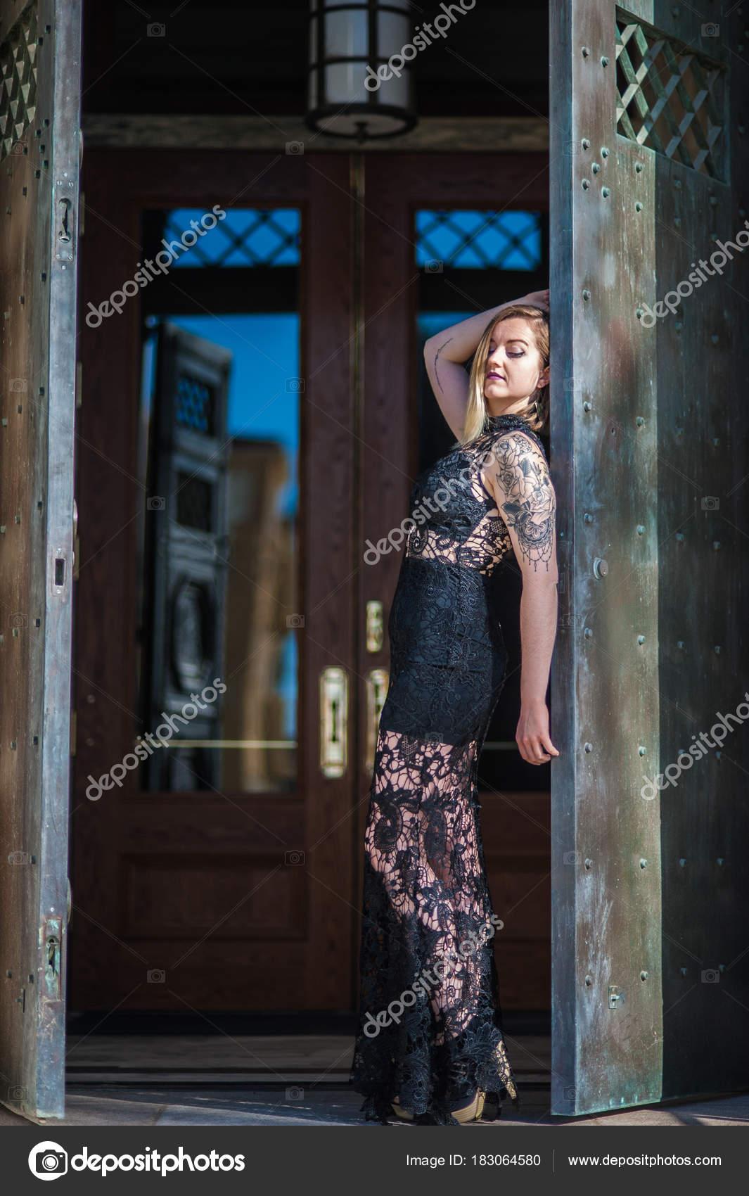 575bd0c5ca2 Rustikální dveře otevřené odhalila alternativní model v černé krajkové  večerní šaty se zpět jako sklo odráží modré oblohy– stock obrázky