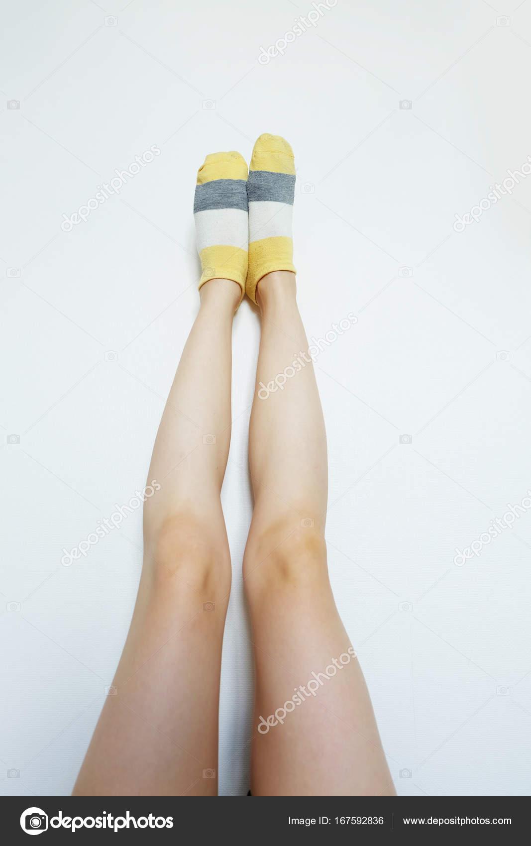 Gestreifte Socken. Frau schlanke Beine und Füße tragen Socken ...