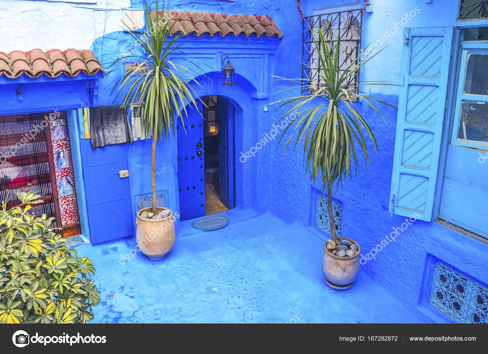 Blauwe muur en trap versierd met kleurrijke bloempotten
