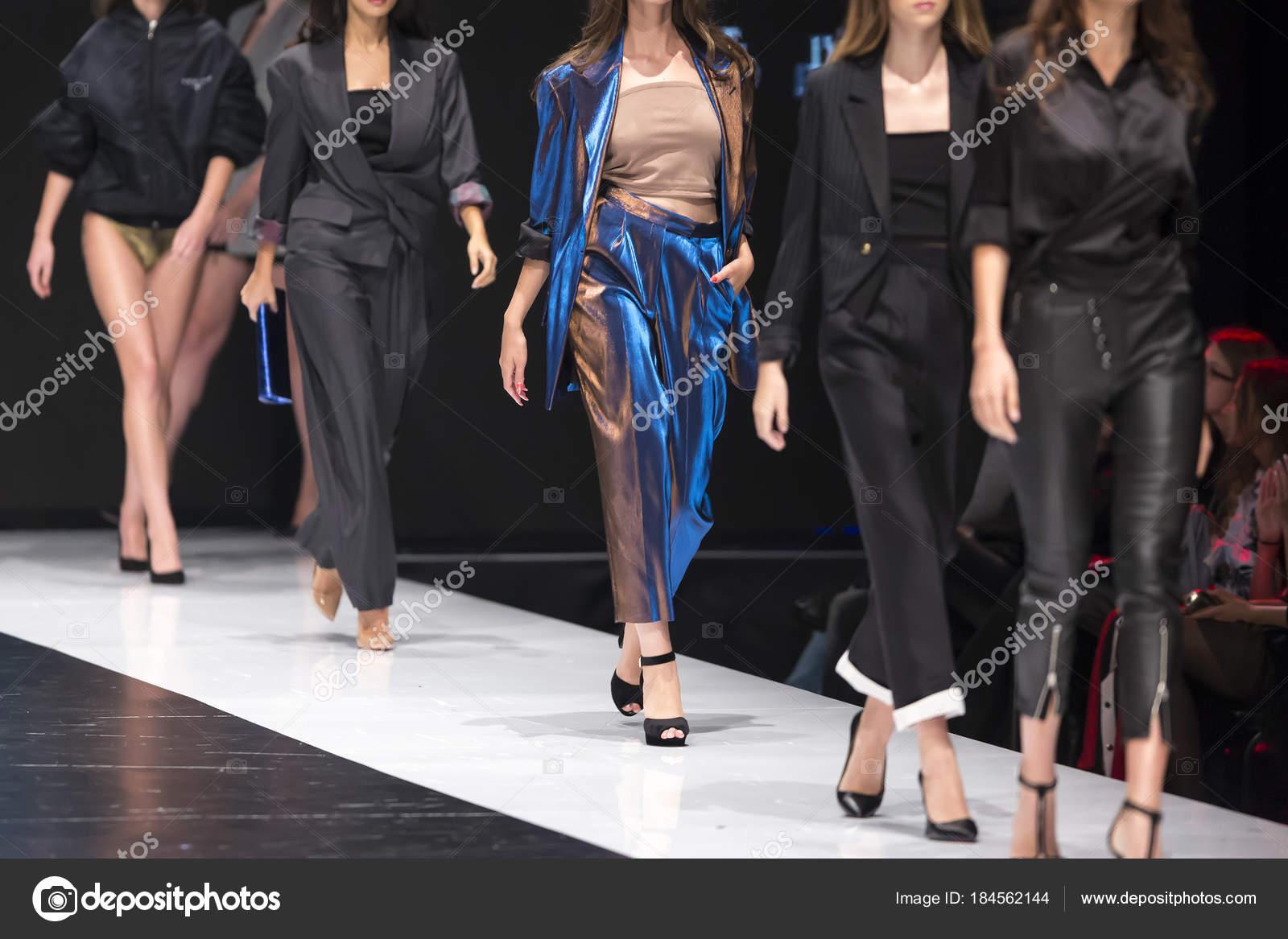3436d93bb3 Modelos femininos andar pista em vestidos diferentes durante um desfile de  moda. Evento de moda passarela mostrando a nova coleção de roupas.