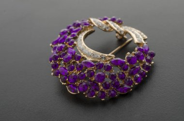 golden round brooch with purple diamonds isolated on black