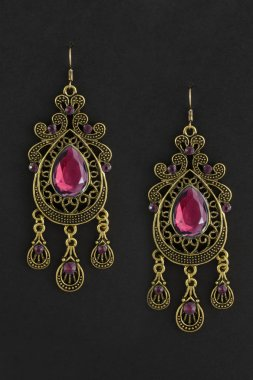 gold earrings with crimson stones isolated on black
