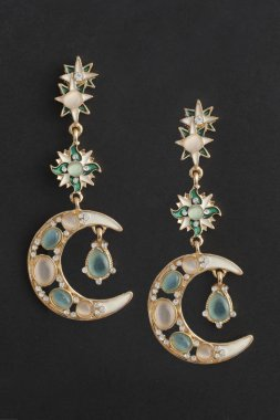 gold earrings moon, with a lunar stone isolated on black