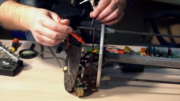 Elektrik testet mit Voltmeter für Reparatur elektronischer Geräte