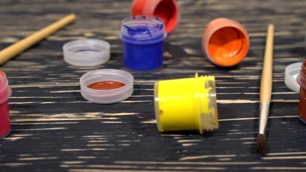Mnoho pestrobarevný barva kvaš sklenice s kartáči na dřevěné pozadí