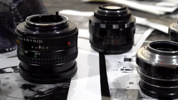 Vintage 35mm cameras, lenses, photos and film are piled up.