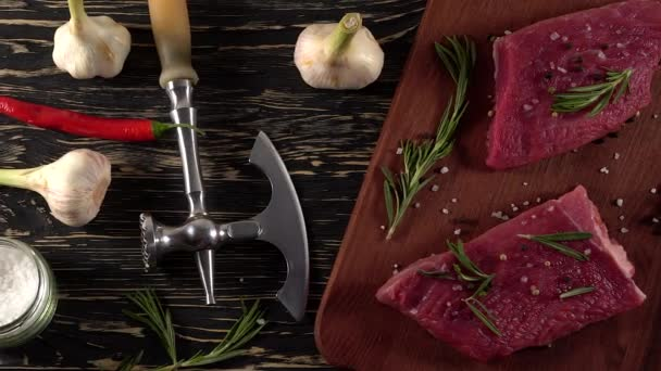 Beef fillet on a desk with pepper, rosemary axe and garlic.