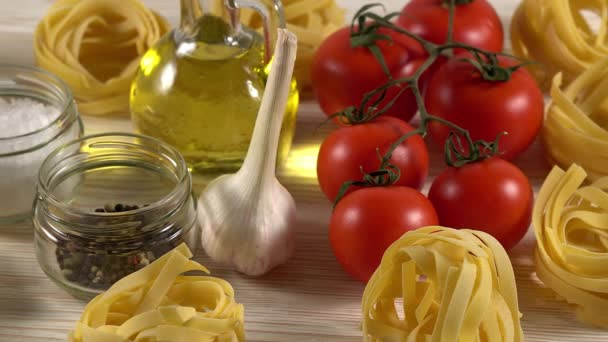 pasta, oil, tomatos and garlic on wooden background