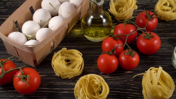 pasta, eggs, oil, tomatos and garlic on wooden background