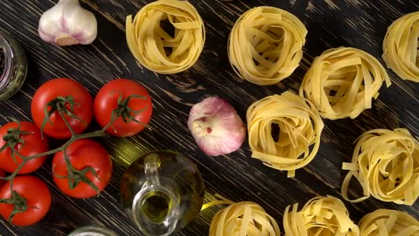pasta, oil, tomatos and garlic on wooden background