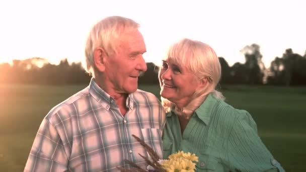Älteres Paar mit Blumenstrauß lächelnd.