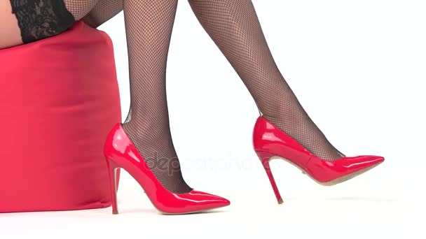 Female legs wearing red shoes.