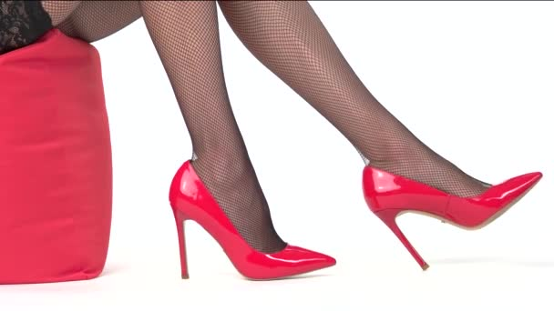 Womans legs wearing red shoes.