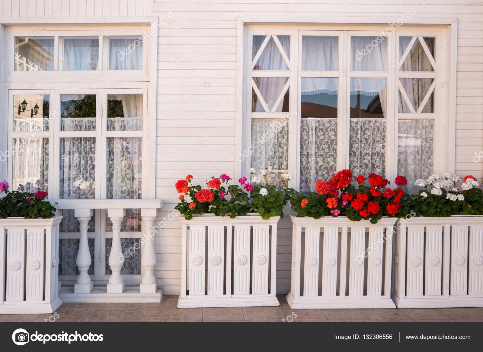 Flowers outside the house. \u2014 Stock Photo © Denisfilm 132306556